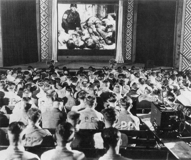 German POWS are forced to watch footage from concentration camps. The view from the back of the auditorium.